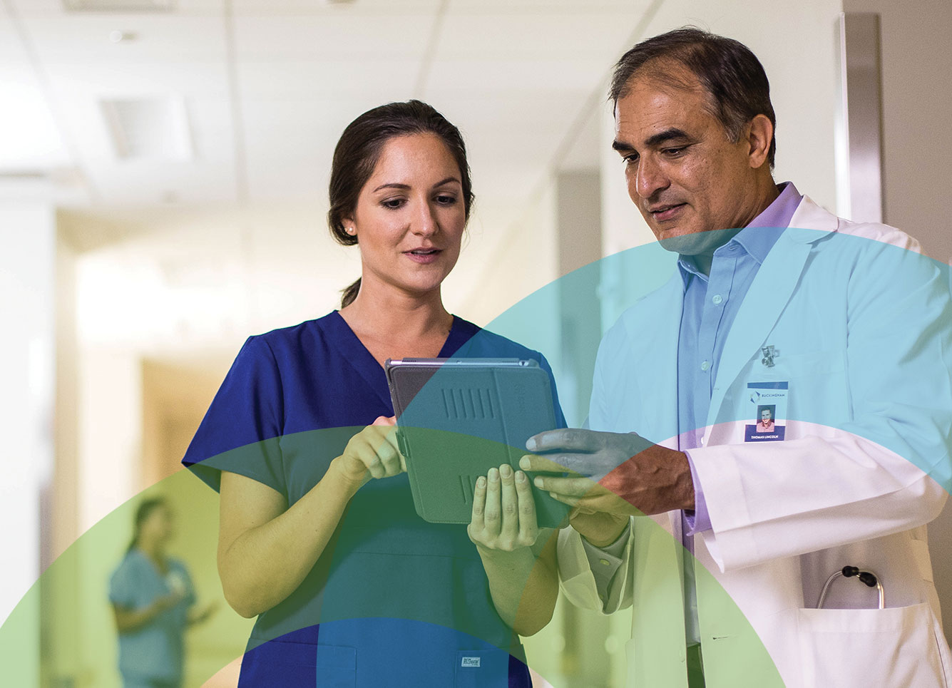 Physician and nurse in clinical setting on tablet, data