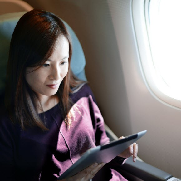 image of woman traveling on a plane looking at an iPad