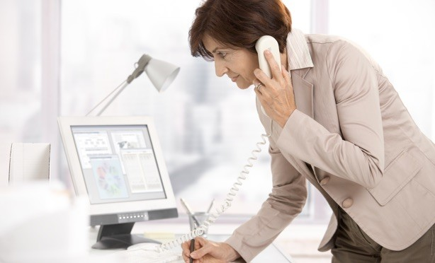 A woman on the phone, taking notes while looking at a computer screen with charts and account information on screen