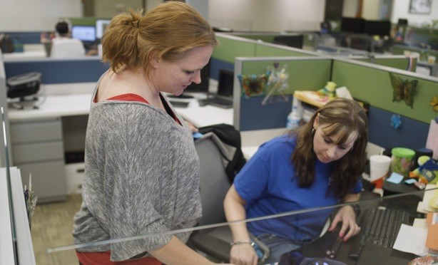 Two women conversing in a office cubicle around a computer