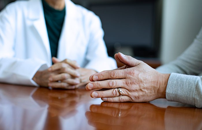 physician and patient hands at table discussing treatment options.