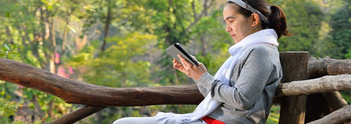 Woman reading electronic device, outside