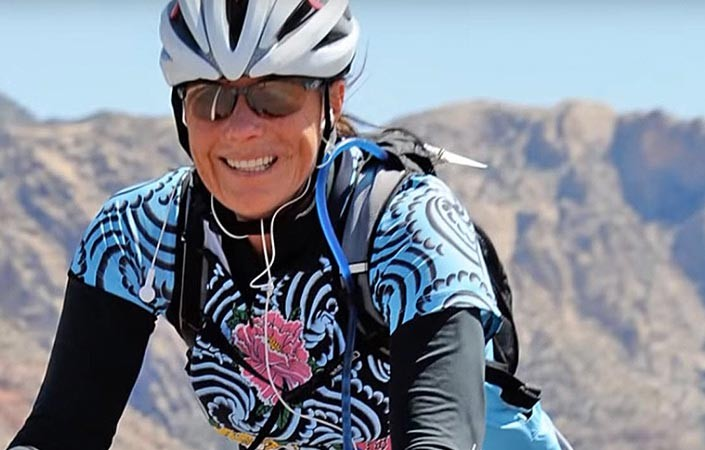 Female Bike Rider, Smiling, on a Trail with a Mountain Backdrop