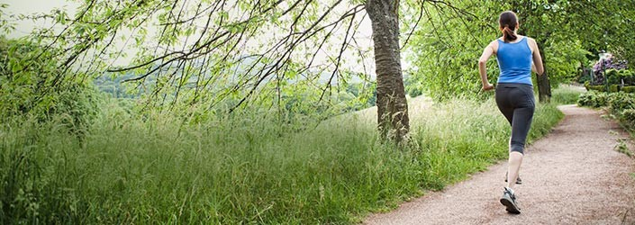 Woman jogging on trail in forest