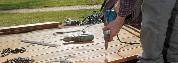 Man using a household appliance, an electric drill, to drill a screw into wood