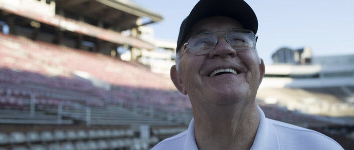 Watchman patient Billy, smiling while standing in a football stadium