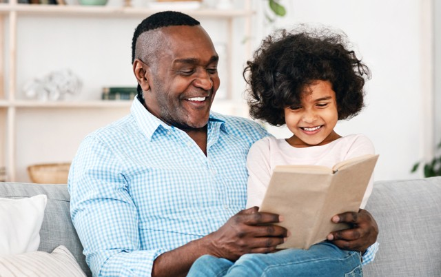 man and young girl reading book