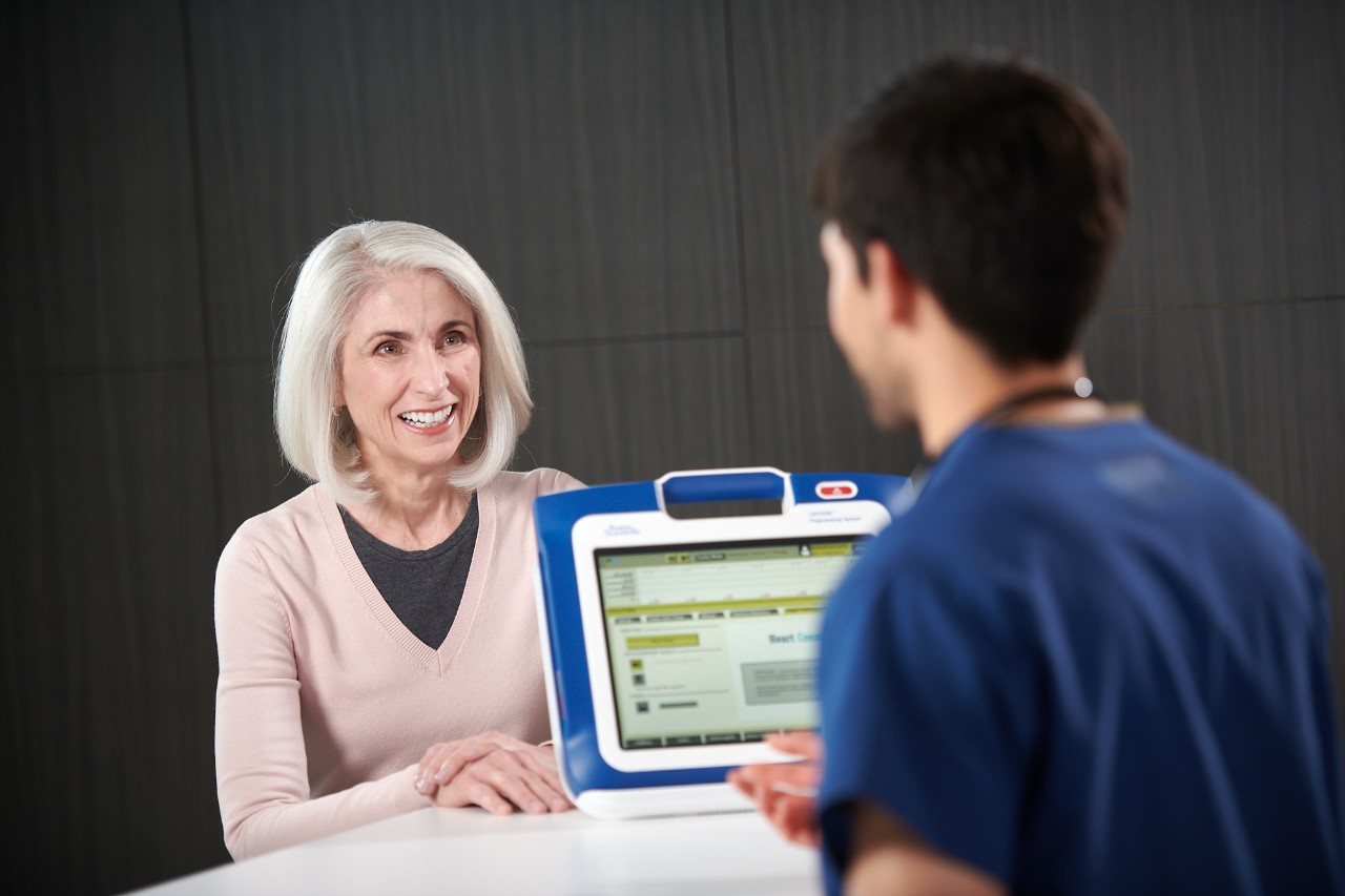 A clinician conducting a device check on a patient using LATITUDE Consult.