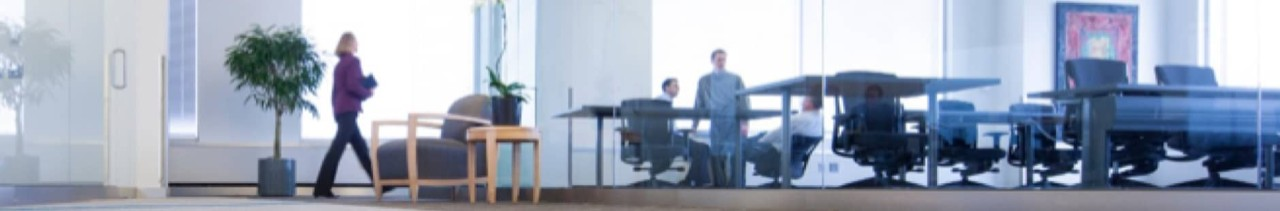 Business men and women walking throughout an office space